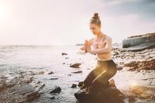 Attractive Girl Prays And Practicing Yoga On The Beach. Healthy Lifestyle, Biohacking, Fitness Concept