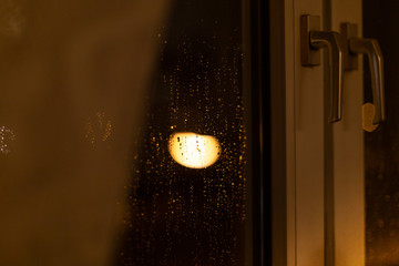 Raindrops on the outside window with a background of Christmas lights.