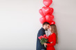 canvas print picture Happy young couple with heart-shaped balloons and flowers on light background. Valentine's Day celebration