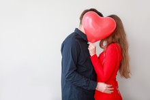 Happy Young Couple With Heart-shaped Balloon On Light Background. Valentine's Day Celebration