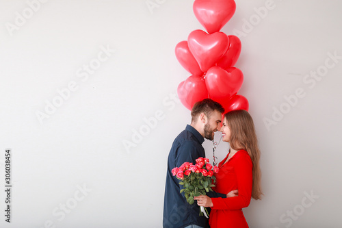 фотография Happy young couple with heart-shaped balloons and flowers on light background