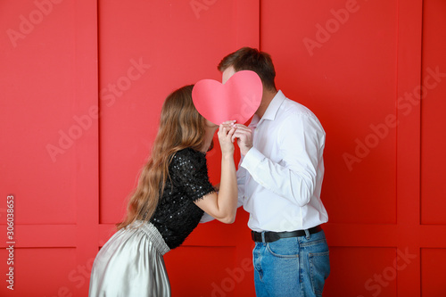 Fototapeta Happy young couple with red heart on color background
