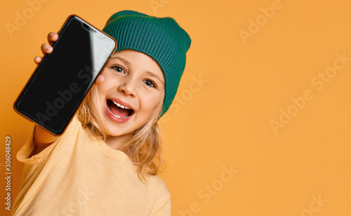 Vászonkép Smiling screaming little girl kid in green modern winter hat showing blank scree
