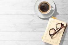 コーヒーカップと本のある白木のテーブル