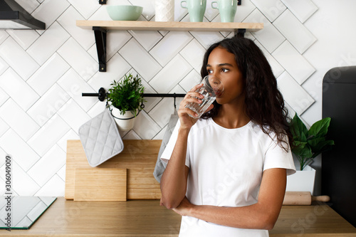 African girl stands on the kitchen and drinks water Fototapet