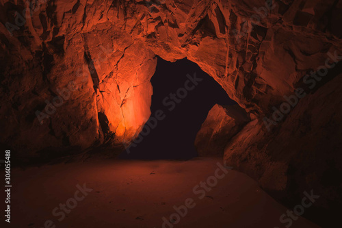 Photo Inside interior of dark underground cave cavern with red light by black hole