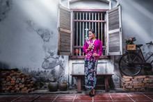Beautiful Asian Woman Wearing Nyonya Dress Her Hand Holding Plastic Flower With Old House, The Dress Of Paranakan Woman In Southeast Asia, Chinese Malay Mix Traditional Costume Asia, Ranong Thailand