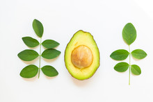 Avocado With Green Leaves On A White Background. Green Healthy Fruit That Is Split In Half And Has A Large Seed Inside.