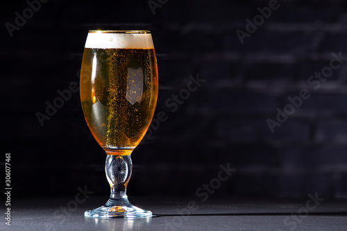 Photo A cups of Stella Artois full of beer with a black brick background