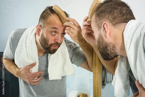 Man using comb in bathroom Wallpaper Mural