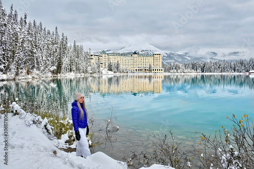 Young sporty woman with blond hair in winter clothes in ski resort by blue alpine lake and mountain lodge Wallpaper Mural