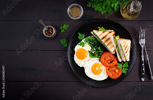 Fototapeta Breakfast: fried egg, spinach, tomatoes and club sandwich on plate. Top view, copy space obraz