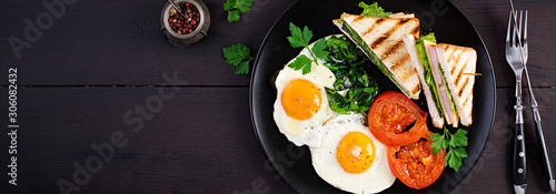 Breakfast: fried egg, spinach, tomatoes and club sandwich on plate Wallpaper Mural