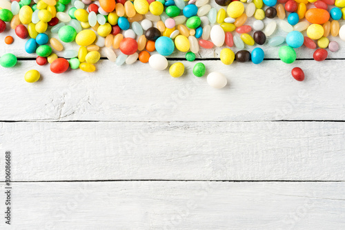 Various kinds of colourful sweets on white wooden table. Top view