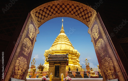 Photo golden pagoda view through from ancient door architrave arch at Wat Phra That Doi Suthep temple