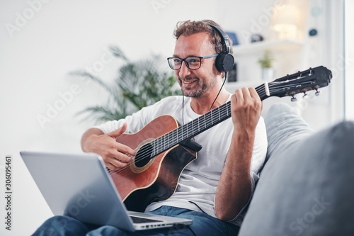 Fotografie, Obraz Man playing acoustic guitar in the living room.