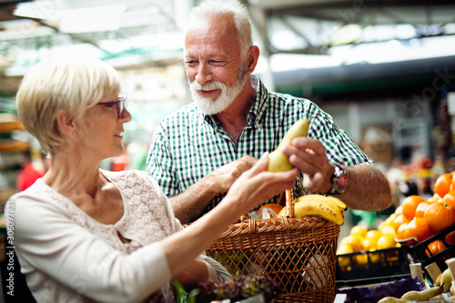 Obraz Mature couple shopping vegetables and fruits on the market. Healthy diet. - fototapety do salonu