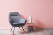 canvas print picture - Soft rocking chair with table and lamp near color wall