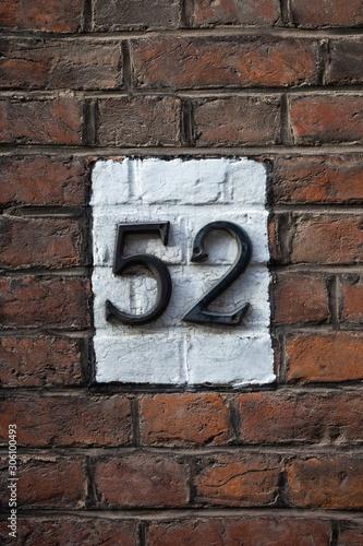 Tela  number 52 on brick wall