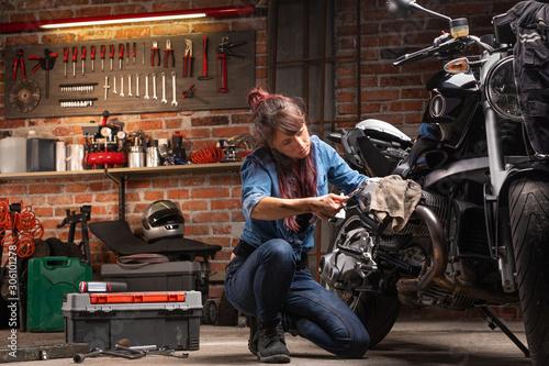 fototapeta na lodówkę Female mechanic working on a vintage bike