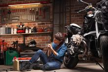Female Biker Or Mechanic Relaxing Smoking