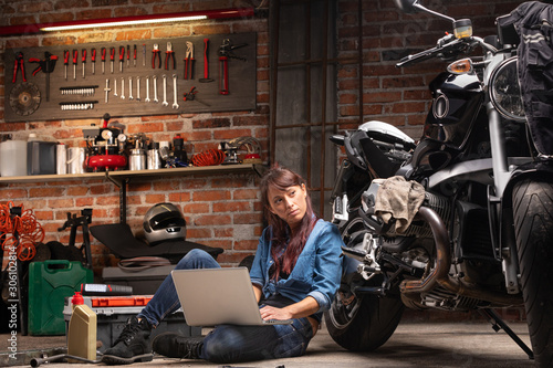 Female mechanic checking for motorbike parts