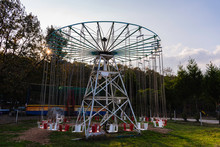 Ferris Wheel In The Park. Empty Rotating Swing Waiting For Children.