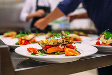 Cooking A Delicious Main Course In The Restaurant Kitchen. Catering On Holiday.