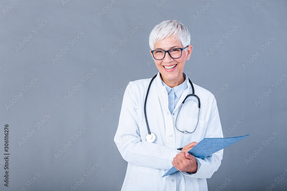 Fototapeta Happy smiling senior female doctor writing on clipboard, isolated on background. Medicine and health care concept. Smiling mature medical doctor woman with stethoscope.