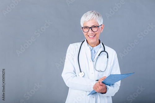 Stampa su Tela Happy smiling senior female doctor writing on clipboard, isolated on background