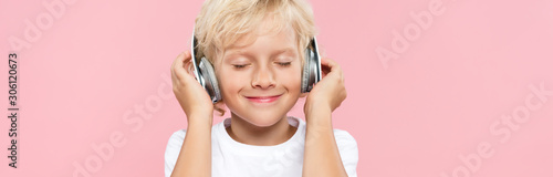 Fotografia panoramic shot of smiling kid with headphones listening music isolated on pink