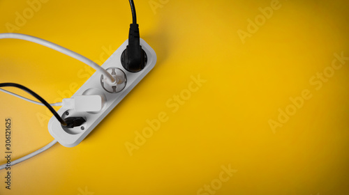 electricity consumption - electric extension cord full of power plugs on yellow background with copy space Fototapete