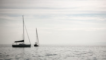 Lake Garda, Italy. A Pair Of Yachts Floating Gently On The Calm Waters Of The Italian Lake District.