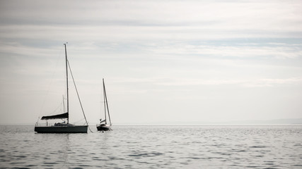 Fototapeta Vintage Lake Garda, Italy. A pair of yachts floating gently on the calm waters of the Italian Lake District.