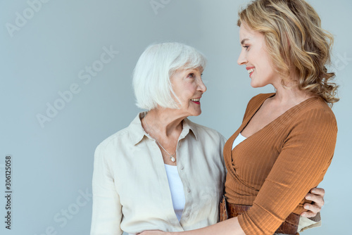 Stampa su Tela smiling mother and daughter hugging and looking at each other isolated on grey