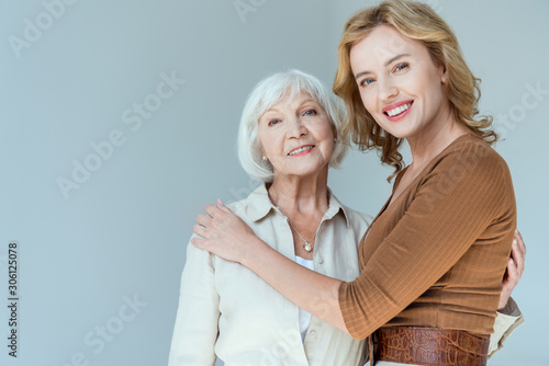 smiling mother and daughter hugging and looking at camera isolated on grey