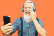 canvas print picture - Senior bearded man taking selfie with mobile phone while listening favorite playlist with headphones - Trendy hipster male having fun with smartphone social apps outdoor - Elderly, technology concept