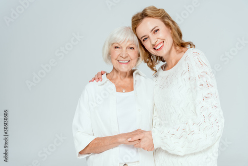 Fototapeta attractive daughter hugging smiling mother and looking at camera isolated on grey obraz