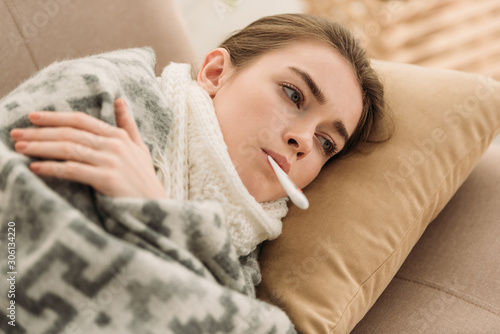 ill woman lying on sofa under blanket and measuring temperature Canvas Print