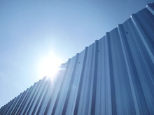 Horizontal Silvery Galvanized Walls And Bright Blue Skies Along With The Sun Light On The Blue Sky Background With Copy Space