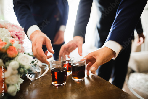 Foto auf Leinwand Alkohol Business meeting. Men hold glasses of whiskey. Men's Party. Hand with a drink of alcohol