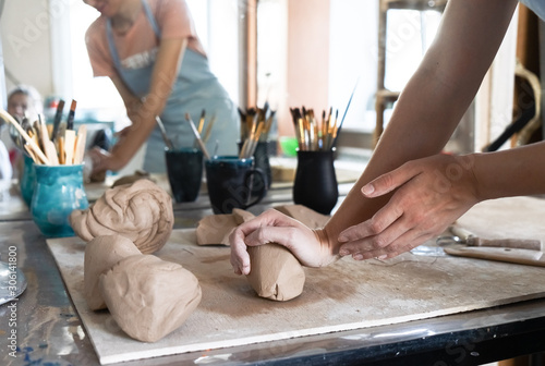 Cuadros en Lienzo A Potter girl kneads a piece of clay with her hands in her Studio workshop