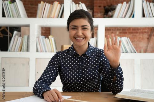 Photo Happy indian female student waving hello at camera.