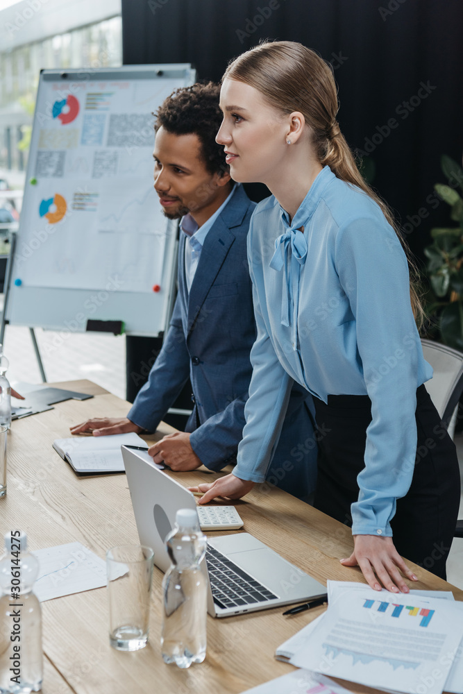 Fototapeta attractive businesswoman with african american colleague standing near desk in meeting room