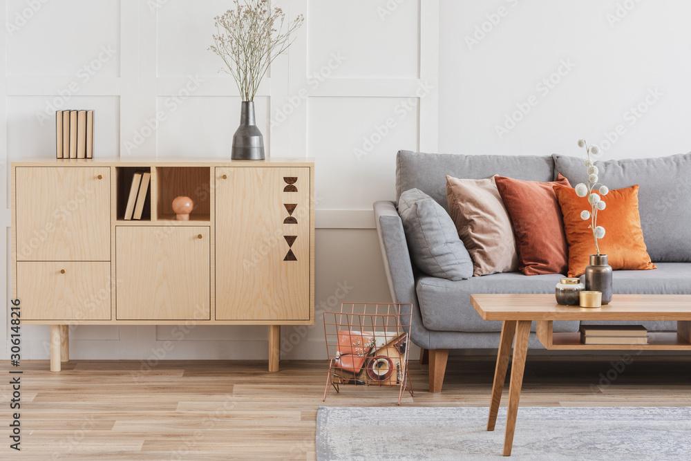 Fototapeta Wooden furniture and grey scandinavian sofa with pillows in beautiful living room interior