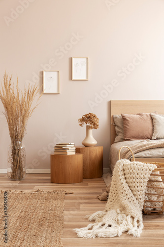 Fotografering Beige kid's room with wooden nightstand with flowers and single bed and wicker b