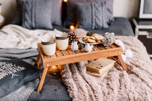 Table With A Cup On The Bed, Marshmallow And Christmas Cookies, Cozy Knitted Blanket. New Year 2019, Flat Lay. Christmas Composition With A Cup Tray And A Mug