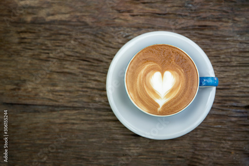 Cup of cappuccino with latte art on old wooden table. Top view,