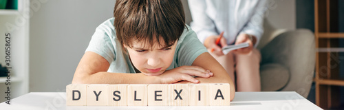 Fotografía panoramic shot of sad kid with dyslexia sitting at table with wooden cubes with