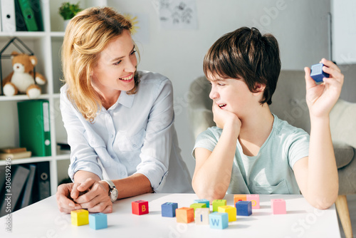 smiling child psychologist looking at kid with dyslexia and sitting at table wit Wallpaper Mural